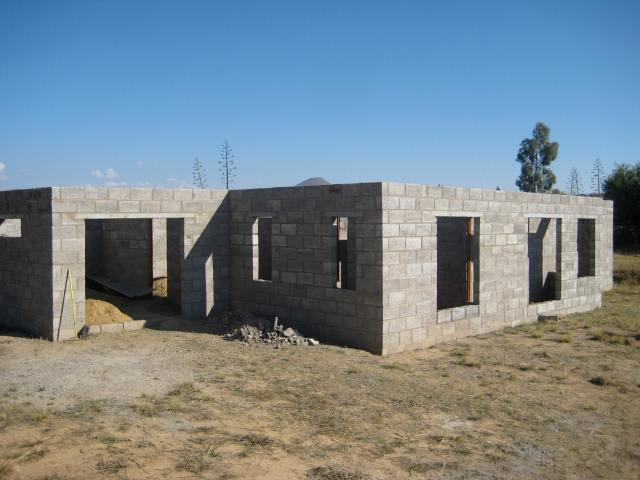 All the walls are officially complete! This view shows the garage on the left, the front window, and porch on the right.